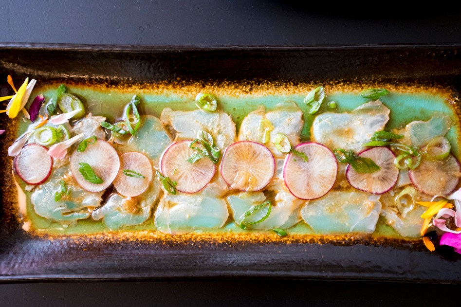 A plate of Yellowtail Crudo served with yuzu soy and ginger.