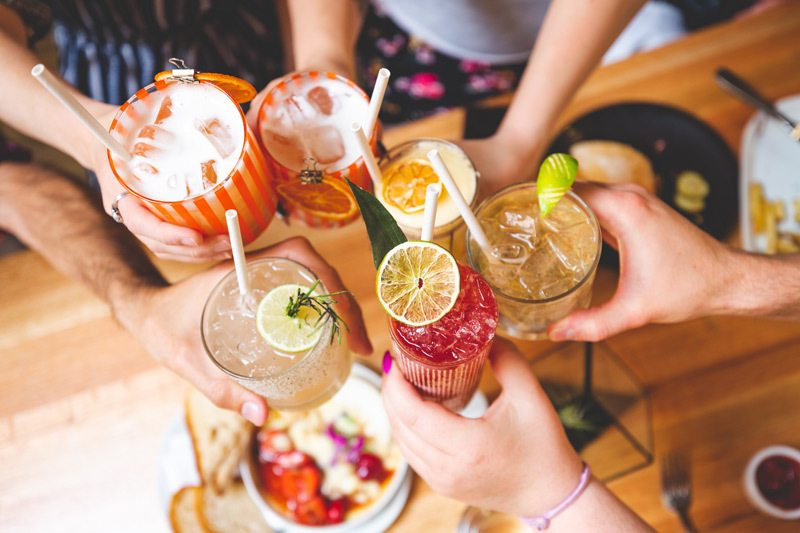 A group of friends say cheers with a collection of creative cocktails.