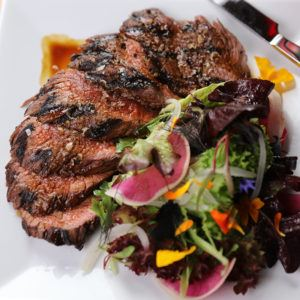 sliced hangar steak and salad on a white plate